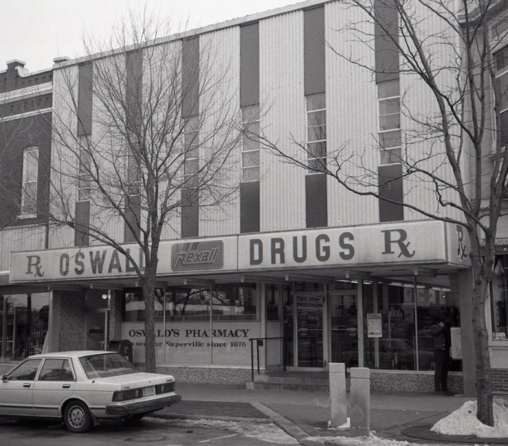 Oswald's Pharmacy exterior shot, 1985. The storefront had been updated at this point. It is day time, so the 'Rexall Oswald Drugs' sign is not lit up. A car manufactured in the 1980s is parked out front.