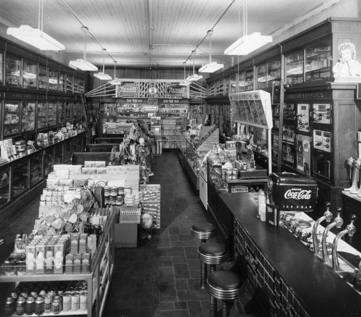 Oswald's interior, 1950. A shot of the whole interior--it is a large, long and narrow room. A soda fountain is featured in the front, with 4 stools. Many old products are squeezed into the limited shelf space.