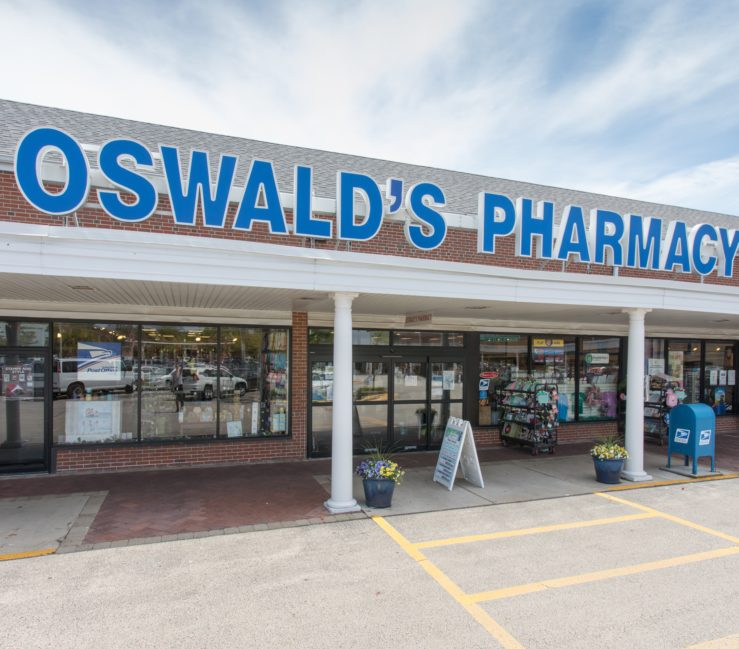 Oswald's Pharmacy, new location, 2016. The front of Oswald's at it's newest location in Naperville Plaza. Blue light up letter's spell out Oswald's Pharmacy on the roof. A sandwich sign sits a few feet in front of the automatic front doors.
