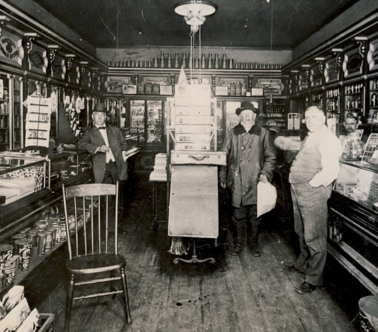Oswald's Pharmacy interior in 1897. Wood floors, wood cabinets. Glass cases line the walls, filled with various medicinal remedies.
