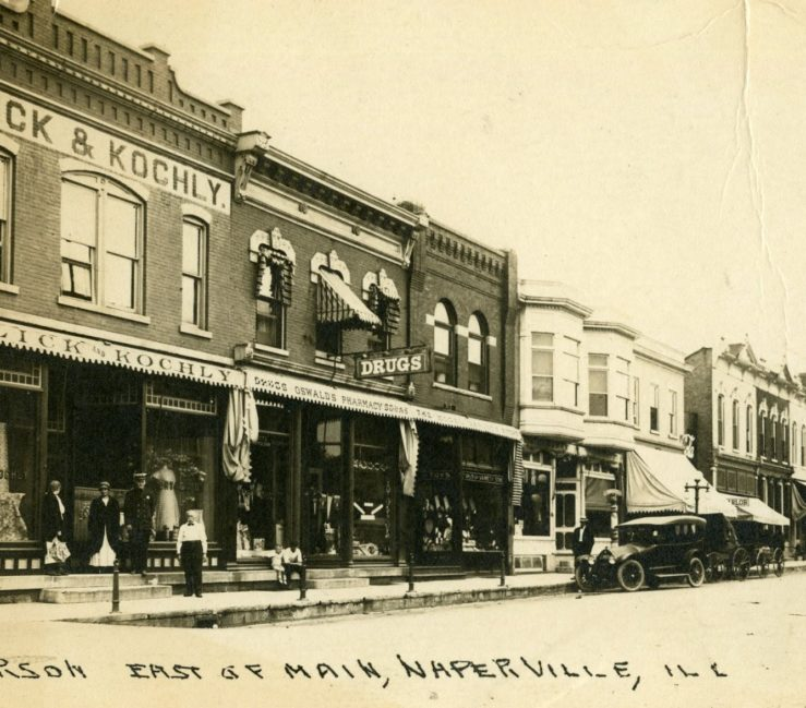 Oswald's Pharmacy exterior in 1925. Jefferson street in downtown Naperville is the setting, showing Oswald's wedged between two other business. An antique car is parked out front.