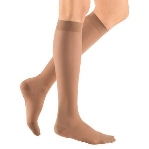 Medi Sheer and Soft compression image. A leg model with a pair of beige, knee-high compression socks.