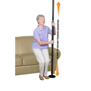 Stander Security Pole standard version. An older woman uses the security pole to help get off of her couch.
