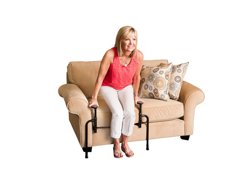 Stander Stand-N-Go being used by a woman to get out of her couch. The black Stand-N-Go bars are tucked under her couch cushion and she is using the handles to push up.