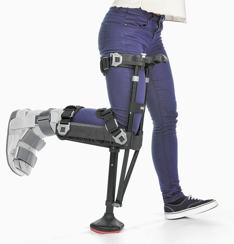 iWalk 2.0 shown on the right leg of a female model wearing jeans. The iWalk is a peg-leg style device; all black with a wide tip. The leg using the iWalk bends at a 90-degree angle and sits in a cradle, while the iWalk base acts as a 'foot.'