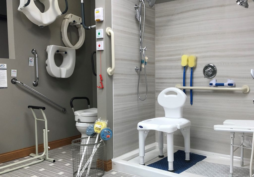 One Stop Post Op Shop Featured Image. A diagonal shot of the Oswald's Medical Equipment Showroom mock bathroom. Many pieces of bathroom safety equipment next to a real toilet and shower. Try before you buy.
