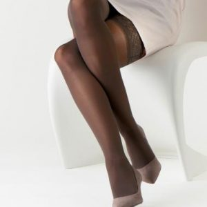 Sigvaris Well Being hosiery worn by a model wearing a white skirt sitting on a white chair. The stockings are black and the background is white.