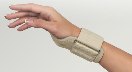 FLA Carpalmate Wrist Support brace. The beige brace is worn by a model. An adjustable band around the wrist and another that wrap around the hand provide support.