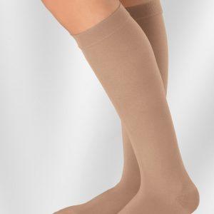 Juzo Compression Hosiery Stockings Soft Basic Casual Dynamic. A leg model wears a knee-high pair of beige Juzo socks.