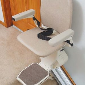 Harmar Pinnacle Premium Straight Stair Lift. An off-white stairlift chair is shown at the top of a stair case. Seatbelt and arms are both locked into, featuring them as a feature.