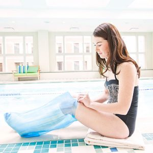 Brown Med Seal Tight Sport Pediatric Cast Protector worn by a female model in a black bathing suit sitting poolside. The cast protector itself is clear blue.