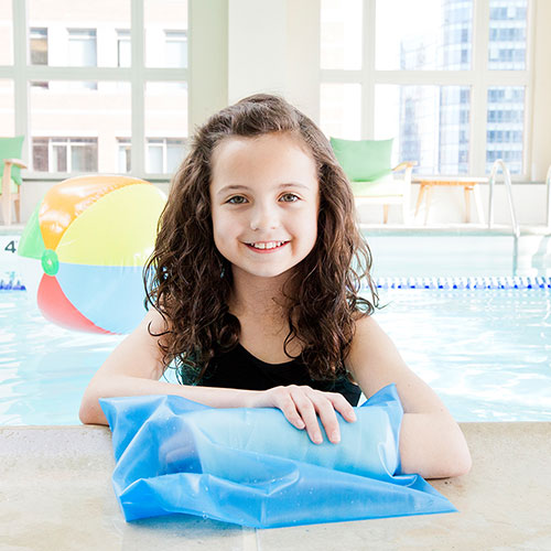 Brown Med Seal Tight Sport Pediatric Cast Protector worn by a child model in a black bathing suit. The cast protector itself is clear blue.