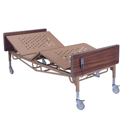 Roscoe Full Electric Bariatric Hospital Bed against a white background. The bed is all beige, excepting the faux wood header and footer and grey wheels. The bed is shown angled at the head and foot, demonstrating its range of motion.