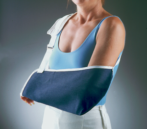 FLA Cradle Arm Sling Denim. The sling is blue and is being modeled by a woman in a blue shirt. Her left arm rests in the sling.