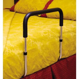 Essentials Endurance Bed Rail shown assembled and wedged between a mattress with yellow sheets and a box spring with red sheets. The rail is silver with black accents.