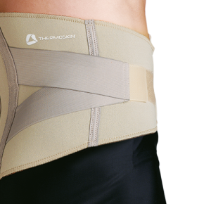 Thermoskin Adjustable Lumbar Support. A model shows off the lumbar support which is tan and has gray criss-crossing, adjustable straps.