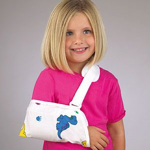 FLA Pediatric Cradle Arm Sling worn by a young girl with blonde hair. Her right arm is in the sling, which is white with various dinosaur graphics.