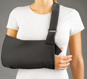 FLA Prolite Universal Arm Sling in black. Worn by a female model, the brace is shown cradling her right arm.