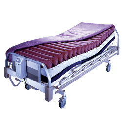Roscoe Genesis Air Mattress Hospital Bed. The genesis mattress is shown on a generic hospital bed (bed not included). The mattress is a series of red, inflatable rolls, which can be adjusted via remote to the patients desired levels.