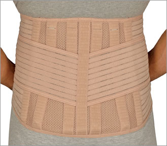 FLA Therall Heat Retaining Back Support. A female model wearing a grey shirt and pants wears the tan support brace. The brace is tan and has many support strips, both vertically and horizontally placed.