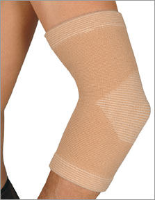 FLA Therall Joint Warming Elbow Support. A models elbow is in the picture, covered by the therall elbow brace. The brace is tan and stretches from the mid-forearm to just under the shoulder.