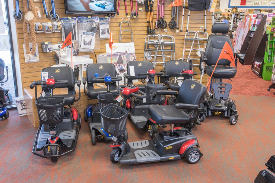 Renting or Purchasing Scooters featured image. The front section of Oswald's Medical Equipment Showroom, 7 mobility scooters can be seen displayed against a wall filled with scooter accessories.