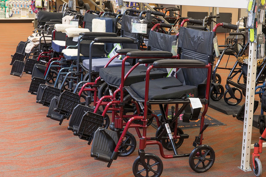 A row of red and blue (alternating) transport chairs available on the Oswald's Medical Showroom floor.