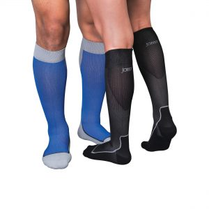 Two leg models wearing Jobst compression sport socks. The left legs belong to a male and are in the knee-high style, blue in color with grey accents. The right set of legs belong to a woman and are in the knee-high style, black in color with grey accents.