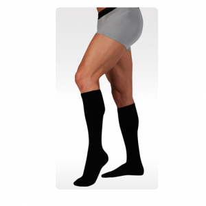 Juzo dynamic cotton compression socks being worn by a male leg model. Knee-high style in black.