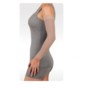 A female arm model wearing the Juzo dynamic arm compression sleeve. The sleeve is tan and stretches from her wrist to shoulder.