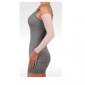 A female arm model wearing the Juzo soft sleeve arm compression sleeve. The sleeve is pink and stretches from her wrist to shoulder.
