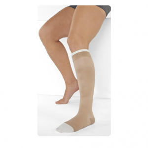 A Male leg model wearing Juzo Ulcer Pro wound care compression. The wrap is tan and is tightly wrapped around the man's leg, starting mid-foot and ending just below the knee.
