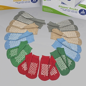 McKesson Slipper Socks product image. A semi circle of pairs of socks. From the top to bottom: XXL Grey, XL Beige, L Light Blue, M Green, S Red. All of the slipper socks have criss crossing slip resistant pads on the bottom.