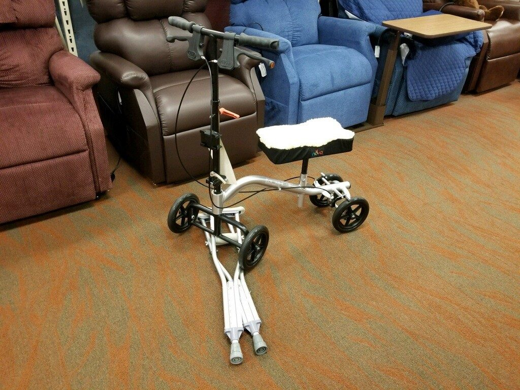 Image of a knee scooter running over a pair of crutches on the Oswald's Medical Equipment Showroom floor. A row of power lift recliners is seen in the background.