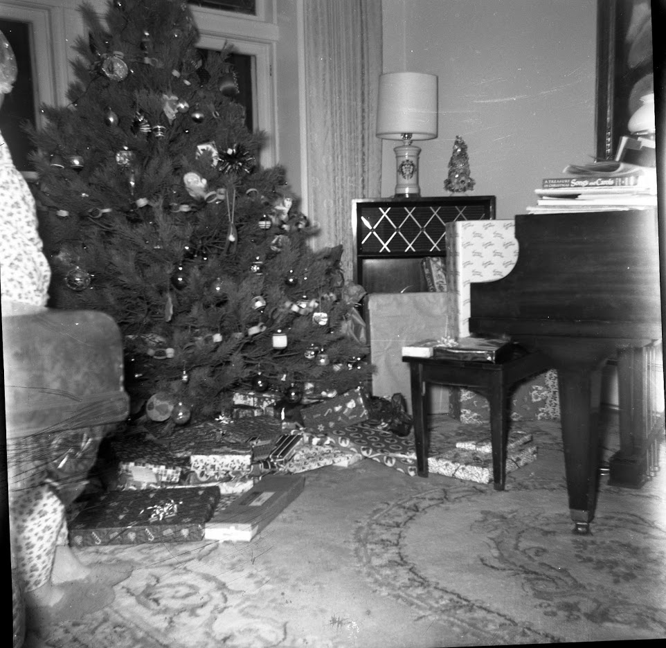 Message from Bill 2018 inset image--Oswald's Pharmacy owner Bill Anderson's home in 1967. Black and white picture of a Christmas tree with lots of gifts underneath.