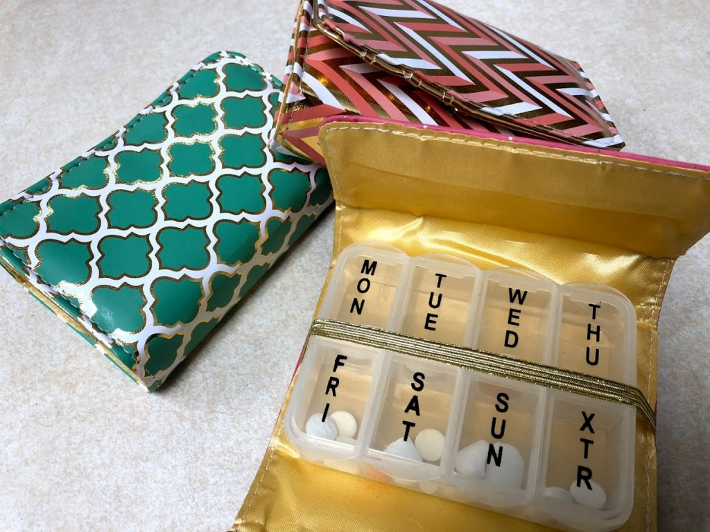 3 decorative pill boxes on the counter at Oswald's Pharmacy. There are many styles available--your pillbox can match your personality!