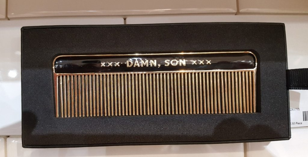 A gold and black metal comb with the phrase 'damn son' printed on it.