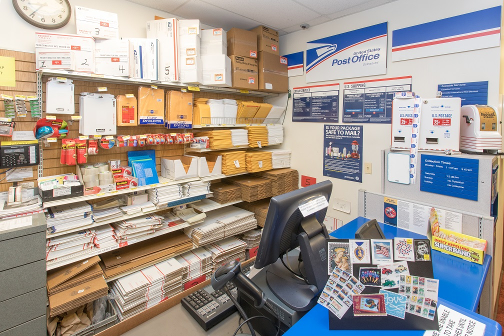 Post Office located in Oswald's Pharmacy. A shot of the post office checkout counter with many USPS signs and envelopes for shipping.