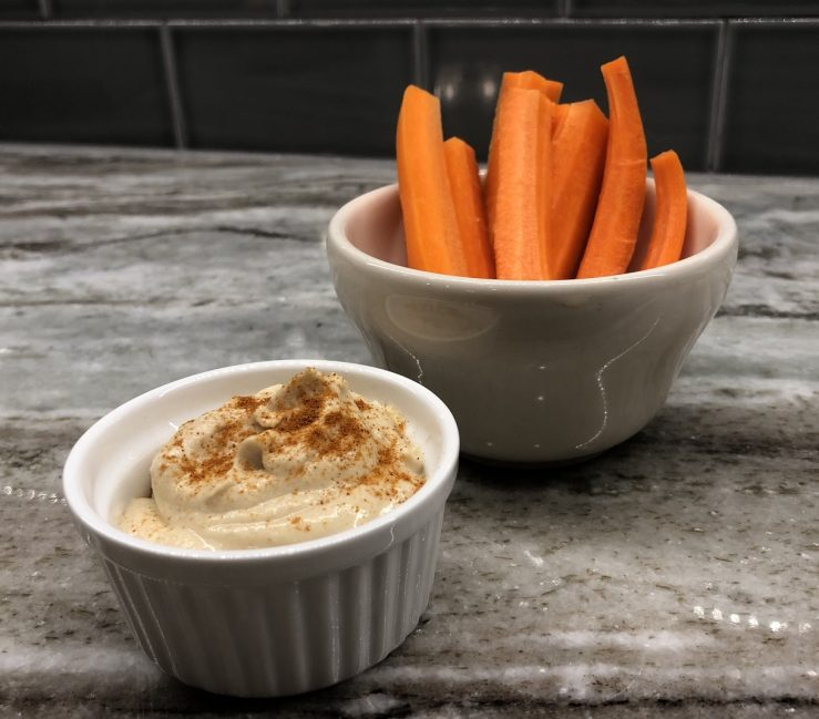 A bowl of carrots next to a bowl of hummus, prepared by Allison.