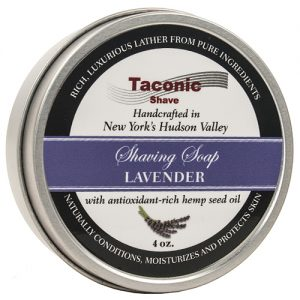 Taconic Lavender Shave Soap. A tin of Taconic's Lavender Shaving Soap. Chrome tin with black highlights and 'shaving soap lavender' written in white in a lavender banner.