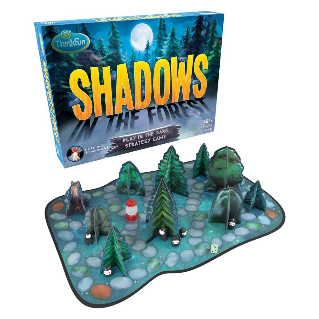 Shadows in the Forest Board Game. Image shows the board game packaging over the board with tree and rock game pieces.
