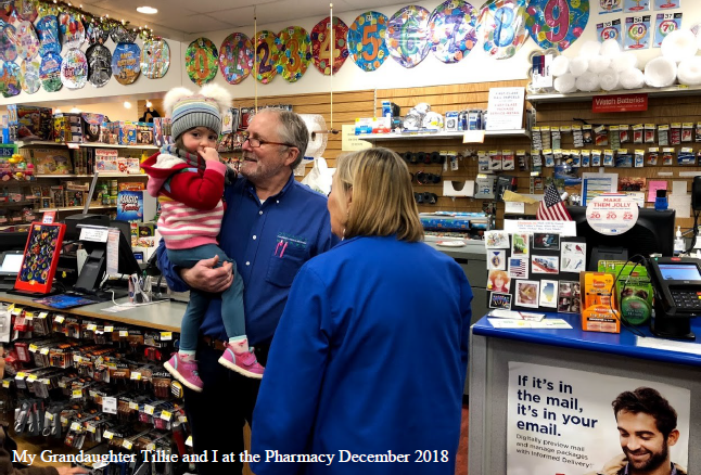Picture of Bill Anderson and his granddaughter at the Oswald's Pharmacy post office counter.