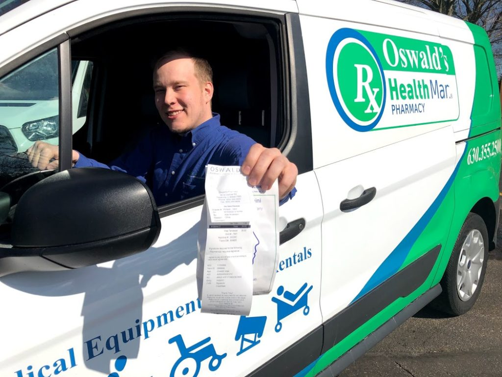 Picture of Oswald's Pharmacy team member Matias delivering a prescription in the Oswald's delivery van.