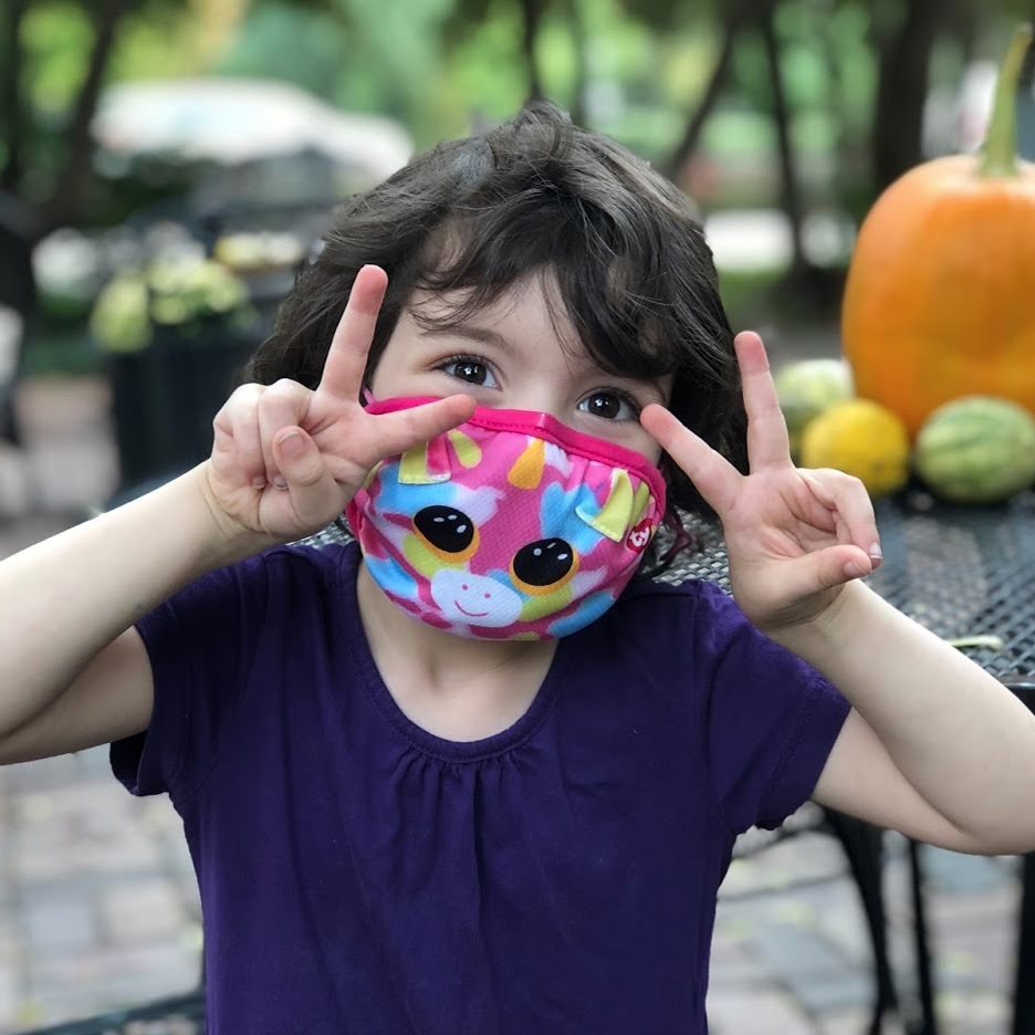 Children's protective face masks image. Photo of a young girl wearing a face mask outside.
