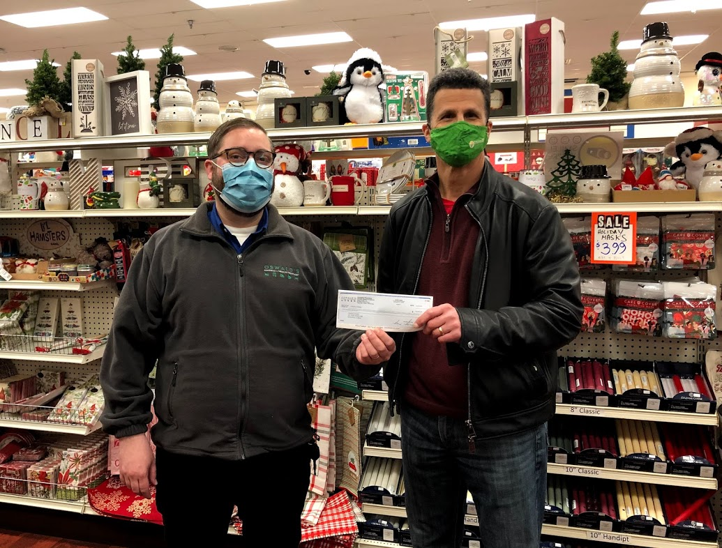 Oswald's Community Partners 2021. Image of Oswald's owner Alex Anderson donating a check to local charities.