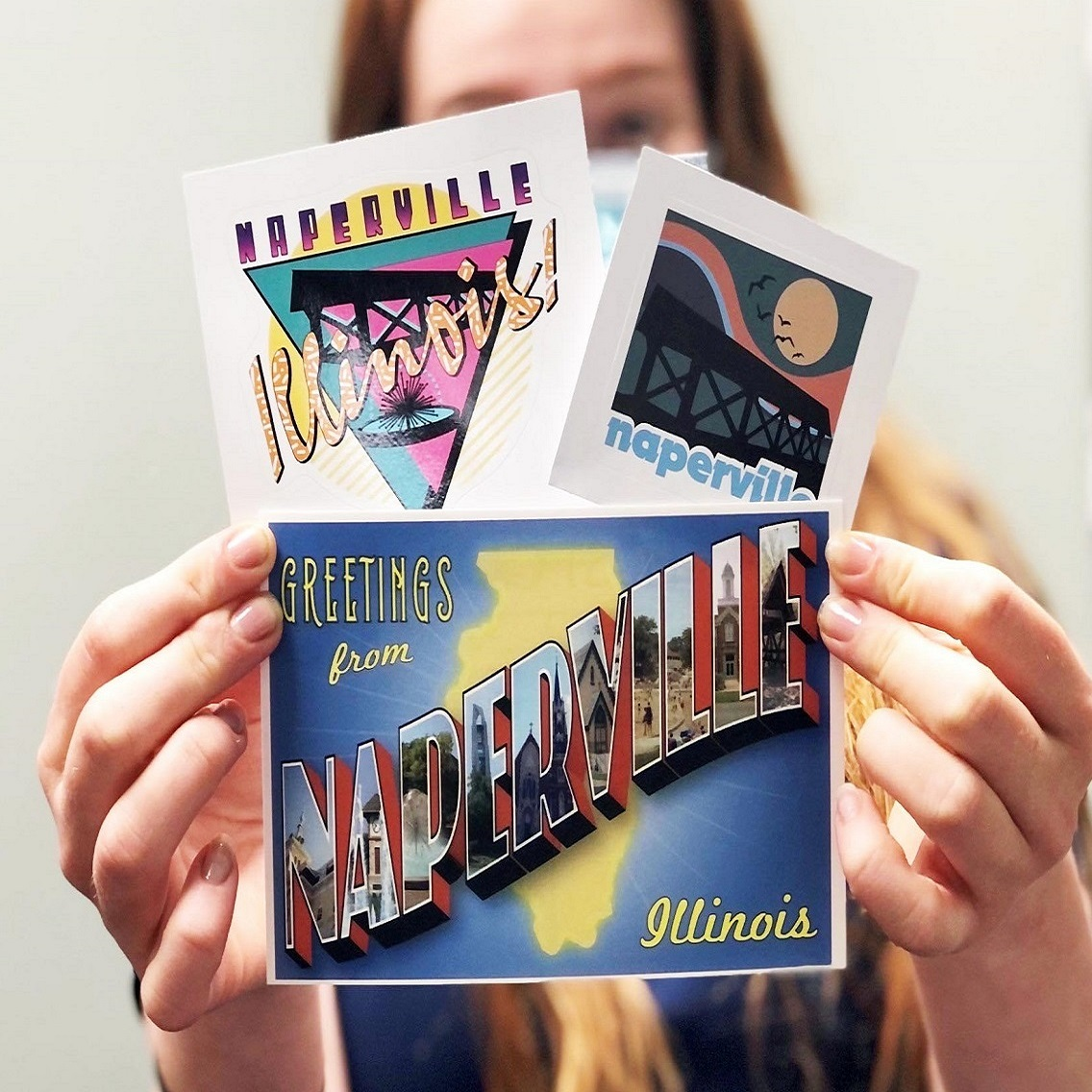Naperville stickers homepage image. A woman holding an assortment of Naperville, IL stickers.